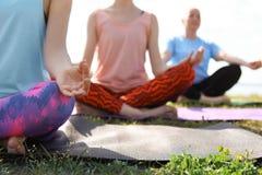 Группа в составе женщины практикуя йогу outdoors Стоковое фото RF