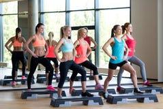 Группа в составе женщины разрабатывая с steppers в спортзале Стоковая Фотография