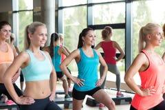 Группа в составе женщины разрабатывая с steppers в спортзале Стоковые Фото