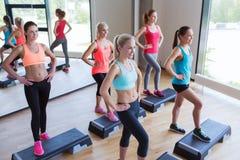 Группа в составе женщины разрабатывая с steppers в спортзале Стоковое Фото