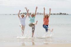 Группа в составе 3 женщины старшия зрелых выбытых на их 60s имея потеху наслаждаясь совместно счастливый идти на усмехаться пляжа Стоковые Фото