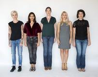 Группа в составе женщины стоит совместно серьезный взгляд Стоковые Изображения RF