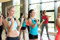 Группа в составе женщины с гантелями в спортзале Стоковые Фото