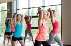 Группа в составе женщины с гантелями в спортзале Стоковые Изображения
