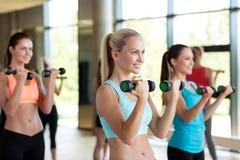 Группа в составе женщины с гантелями в спортзале Стоковая Фотография