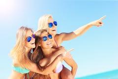 Группа в составе женщины указывая на что-то на пляже Стоковые Изображения RF