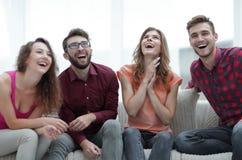 Группа в составе жизнерадостное молодые люди сидя на кресле Стоковое Фото