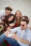 Группа в составе жизнерадостные друзья имея большое время на пляже Стоковые Изображения