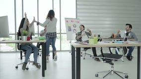 Группа в составе жизнерадостные счастливые азиатские творческие бизнес-леди и люди наслаждаются и имеющ танцы потехи пока работаю акции видеоматериалы