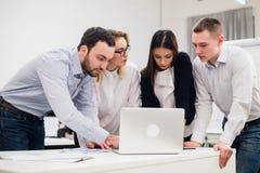 _ Группа в составе жизнерадостные бизнесмены в умной вскользь носке смотря компьтер-книжку совместно и усмехаться Стоковое Фото