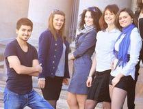 Группа в составе жизнерадостные дружелюбные студенты колледжа на шагах Стоковые Фотографии RF