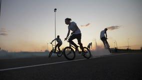 Группа в составе запальчиво велосипедисты выполняя различные фокусы на велосипедах курит приходить из их колес видеоматериал