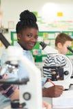 Группа в составе зрачки используя микроскопы в классе науки стоковая фотография rf