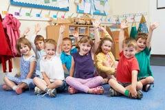Группа в составе зрачки начальной школы кладя руки вверх в класс стоковые изображения rf