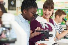 Группа в составе зрачки при учитель используя микроскопы в классе науки Стоковое Фото