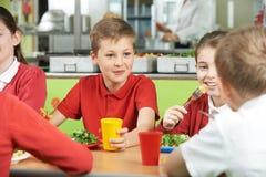 Группа в составе зрачки сидя на таблице в школьном кафетерии есть еду стоковая фотография