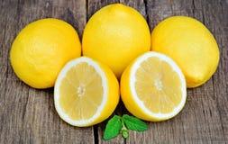 Группа в составе зрелые все желтые цитрусовые фрукты лимона с плодоовощ лимона половинным на таблице Стоковое Фото