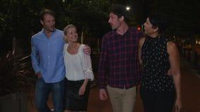 Группа в составе зрелые друзья идя вдоль улицы на ноче вне акции видеоматериалы