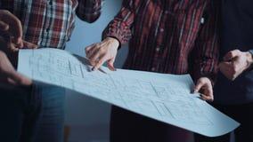 Группа в составе дизайнеры обсуждая светокопии Стоковые Изображения