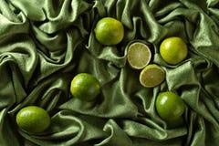 Группа в составе известки всех и отрезка свежие на зеленой сатинировке Стоковая Фотография
