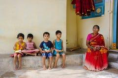 Группа в составе индийские дети сидит на улице и кокосы 11-ое февраля 2018 Puttaparthi еды, Индия Стоковое Фото