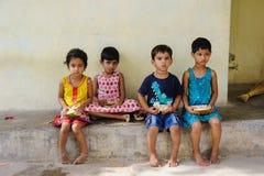 Группа в составе индийские дети сидит на улице и кокосы 11-ое февраля 2018 Puttaparthi еды, Индия Стоковая Фотография RF