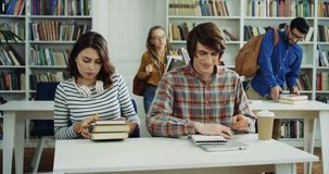 Группа в составе кавказский мужчина и студентки уча в библиотеке, тогда стоя вверх и идя прочь сток-видео