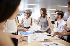 Группа в составе коллеги дела коллективно обсуждать в открытом офисе плана стоковые фотографии rf