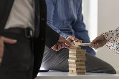 Группа в составе коллеги в офисе тщательно строя башню w Стоковое Фото