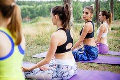 Группа в составе красивые молодые женщины делая йогу совместно Стоковая Фотография