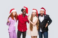 Группа в составе красивые счастливые красивые друзья в красной крышке стоя стоковое изображение