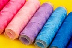 Группа в составе красочные катышкы потока используемые к шить, needlework и вышивке над яркой желтой предпосылкой стоковое изображение