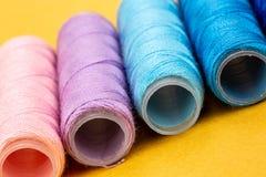 Группа в составе красочные катышкы потока используемые к шить, needlework и вышивке над яркой желтой предпосылкой стоковое фото