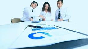 Группа в составе крупного плана диаграмм и диаграмм успешные бизнесмены работая на заднем плане Стоковые Фотографии RF