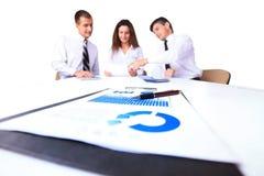 Группа в составе крупного плана диаграмм и диаграмм успешные бизнесмены работая на заднем плане Стоковые Изображения