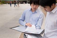 Группа в составе люди дела азиатские стоя и говоря о отчете Стоковая Фотография RF