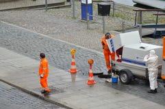 Группа в составе люди работая на чистке сточных труб стоковое фото