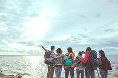 Группа в составе люди смотря солнце и море стоковые изображения rf