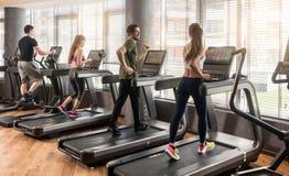 Группа в составе 4 люд бежать на третбанах в спортзале фитнеса Стоковое Изображение