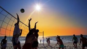 Группа в составе маленькие девочки играя волейбол пляжа во время захода солнца Стоковые Фото