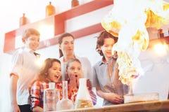 Группа в составе мальчики и девушки проводя химию экспериментируют с учителем Стоковая Фотография RF