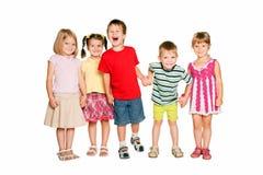 Группа в составе маленькие дети держа руки и усмехаться. стоковое изображение