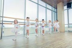Группа в составе 7 маленьких балерин стоя в строке и практикуя балете используя ручку на стене стоковые изображения rf