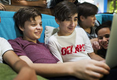 Группа в составе мальчики сидя единение и используя компьтер-книжку Стоковые Изображения