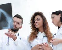 Группа в составе медицинские работники смотря терпеливый фильм рентгеновского снимка ` s Стоковые Изображения