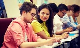 Группа в составе международные студенты писать на лекции стоковая фотография
