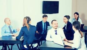 Группа в составе менеджеры при компьтер-книжки имея производительный день Стоковые Фотографии RF