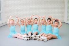 Группа в составе милые маленькие артисты балета смотря камеру на классе школы танцев стоковое фото rf