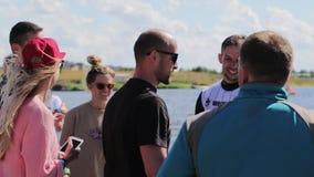 Группа в составе милые молодые люди в красочных одеждах висит вне на реке пристани близрасположенном видеоматериал
