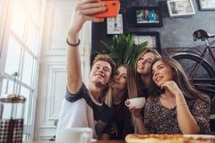 Группа в составе милые подростки принимая selfie с мобильным телефоном пока сидящ в ресторане с интерьером в ретро стиле стоковые фотографии rf
